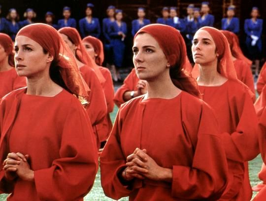 An image of women in red with red head scarves taken from the movie The Handmaid's Tale.