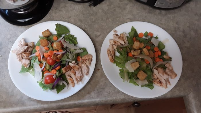 two plates with chicken caesar salad