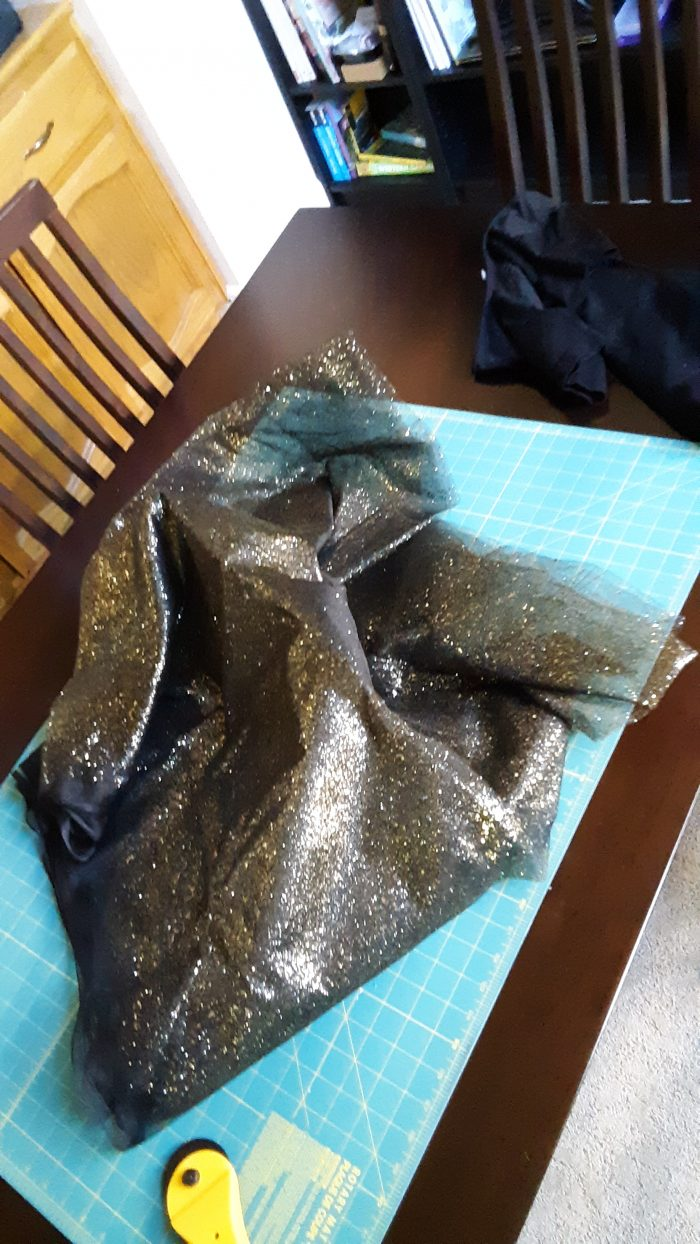 black tulle with gold sparkles on a cutting mat