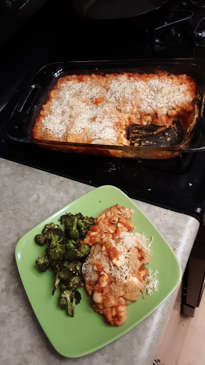 a casserole dish of lima bean parmigiana next to a plate with a serving of the same plus broccoli