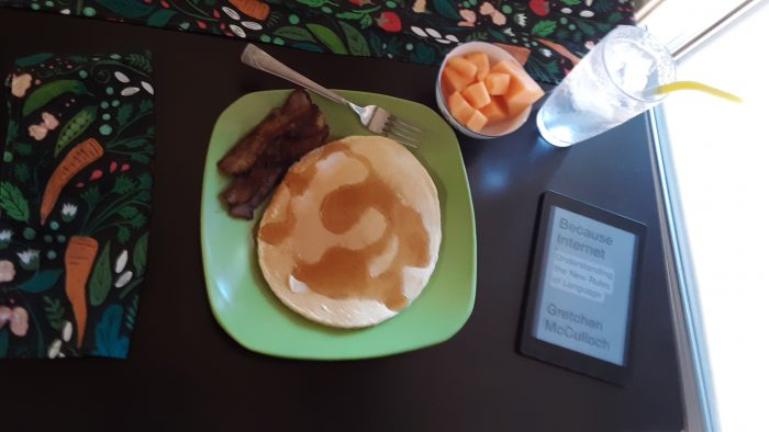 a plate with panckaes and bacon, a small bowl of cantelope, a glass of water, and an e-reader