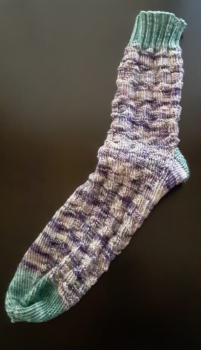a hand-knit sock in variegated purple yarn with green cuff, heel, and toe
