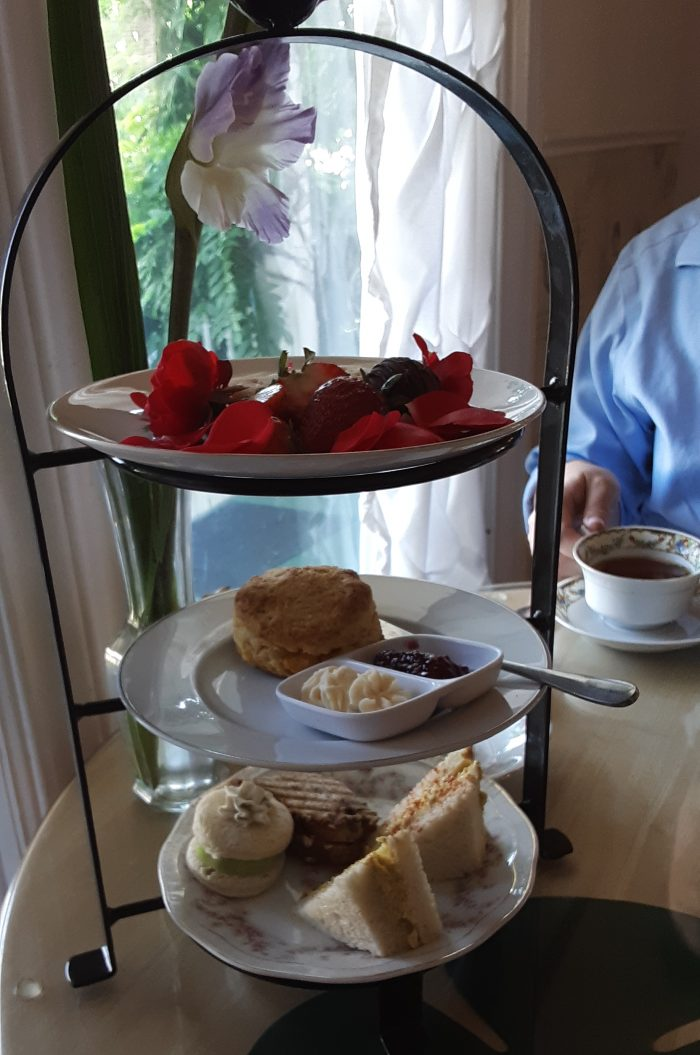 a three-tiered tray of small foods including sandwiches and scones