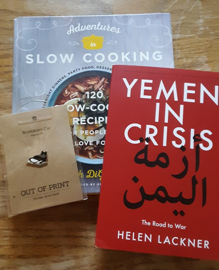 "the books ""adventures in slow cooking"" and ""yemen in crisis"" and an enamel pin of a cat sitting on a book"
