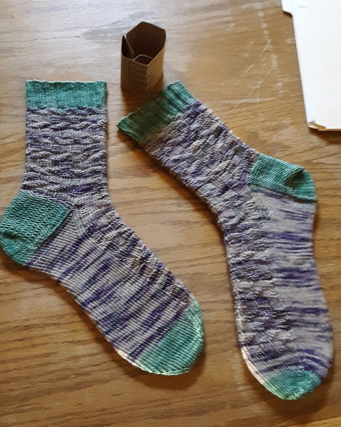 a pair of handknit socks in purple variegated yarn with green cuffs, heels, and toes