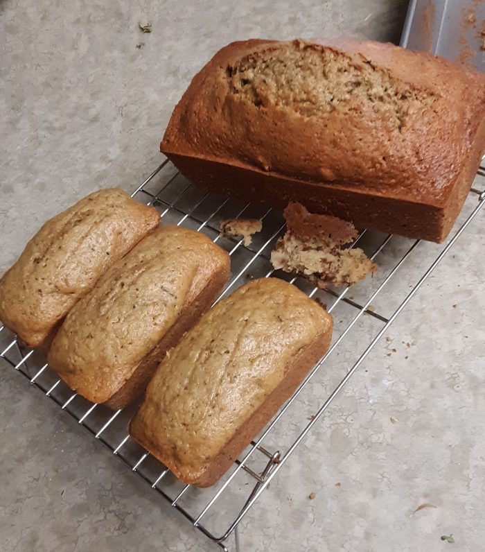 3 small and 1 large zucchini bread loaves on a wire rack
