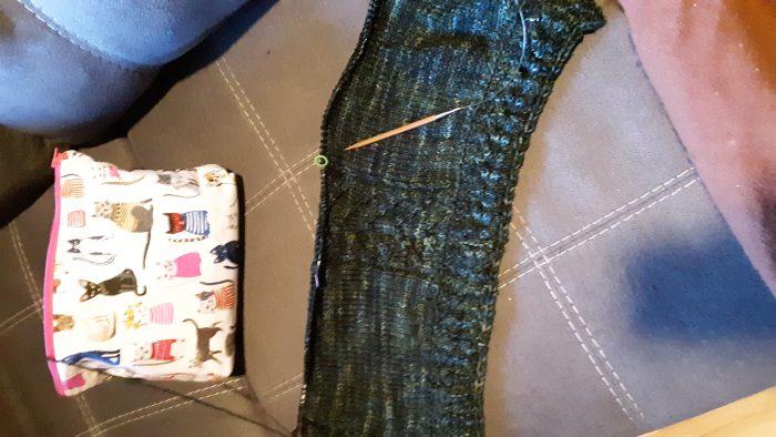 in progress knitting in a dark blue-green yarn