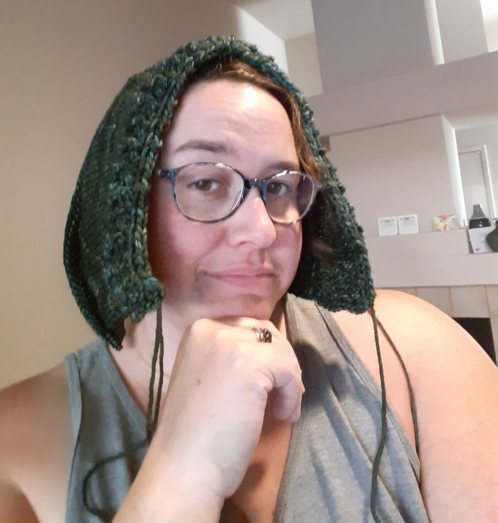 the author with a half-knitted hood on her head