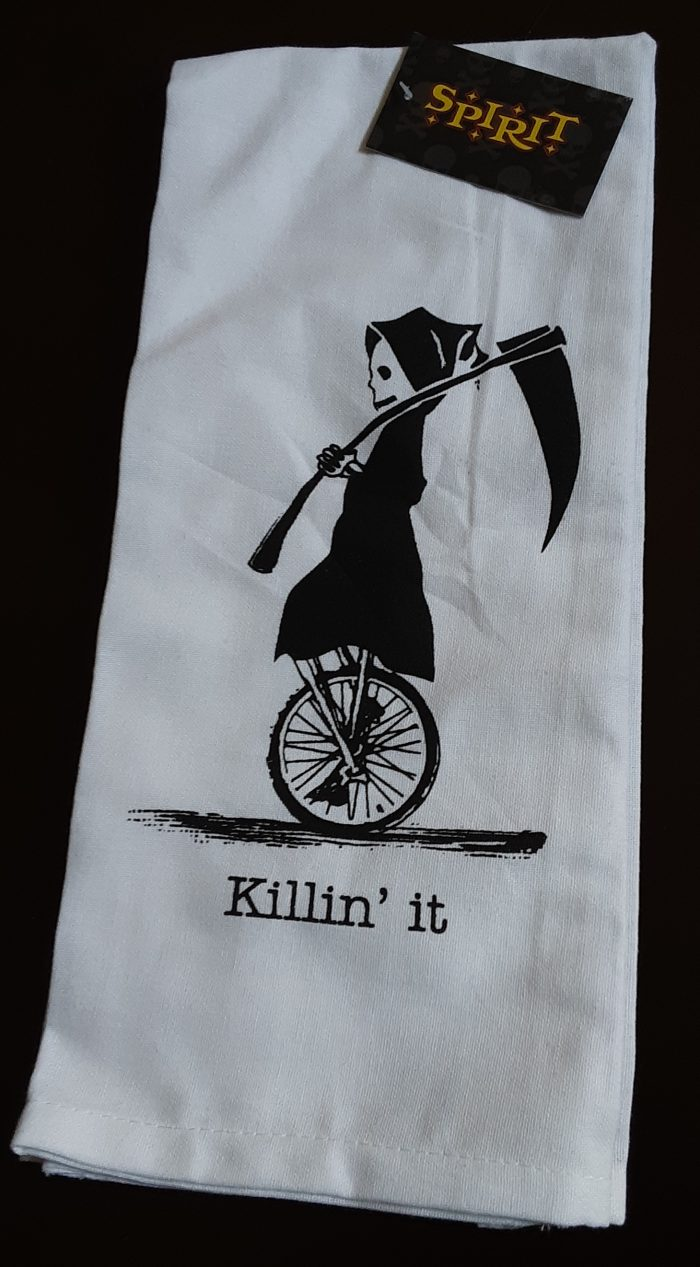 "a white dishtowel with an image of the grim reaper riding a unicycle and the words ""killin it"""
