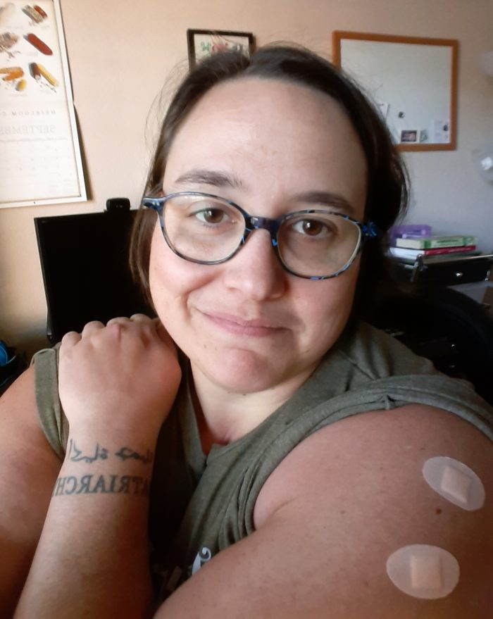 the author showing off her shoulder which has bandaids from getting shots
