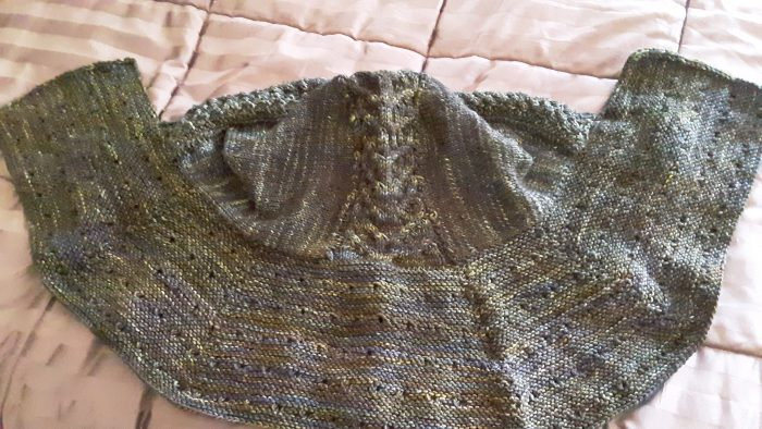 hooded caplet laid out on the bed. Yarn is a variegated forest-y green