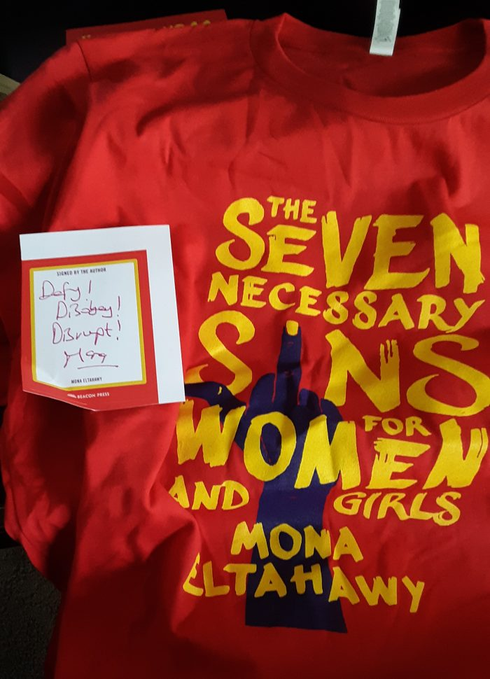 "a shirt with the cover art of ""Seven Necessary Sins for Women and Girls"" and a sticker signed by the author that says ""Defy! Disobey! Disrupt!"""