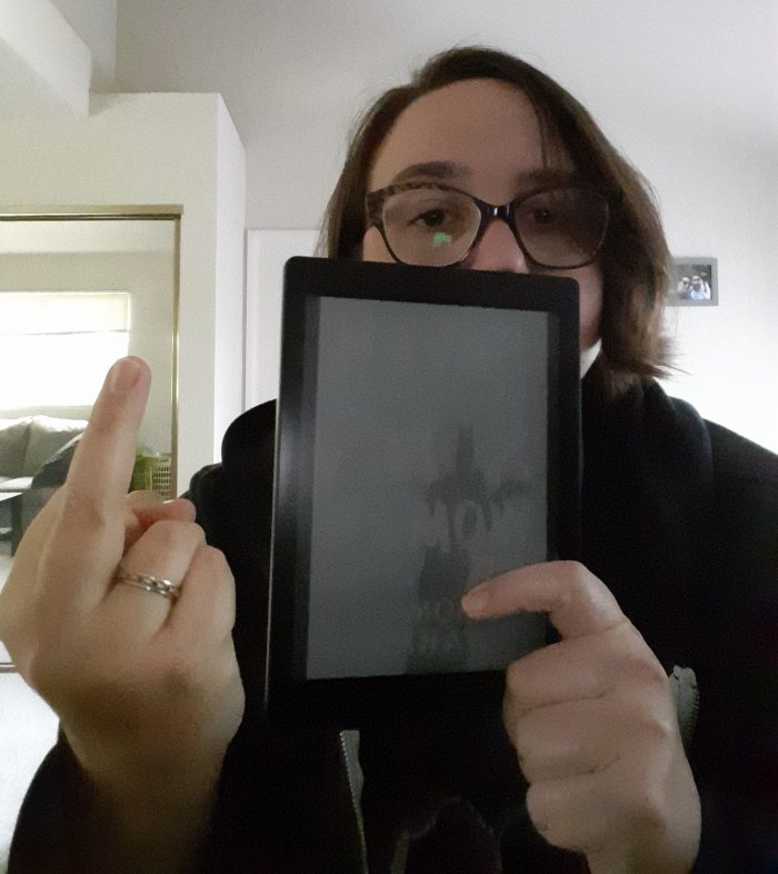 "me holding a kobo reader with the ""seven necessary sins for women and girls cover shown, and putting up my middle finger"