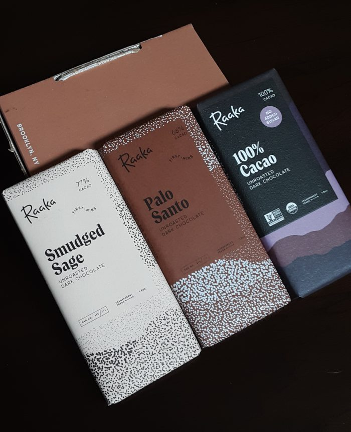 Three Raaka chocolate bars: smudged sage, palo santo, and 100 percent cacao