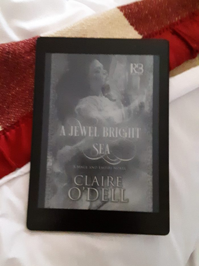 "cover of ""A Jewel Bright Sea"" on kobo reader, background is a bed"