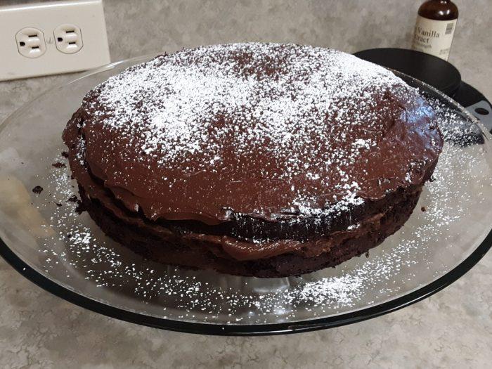 a chocolate cake on a glass cake stand