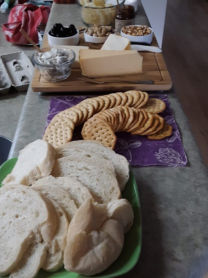 my pre-meal spread: bread, crackers, cheese plate, and other snacks