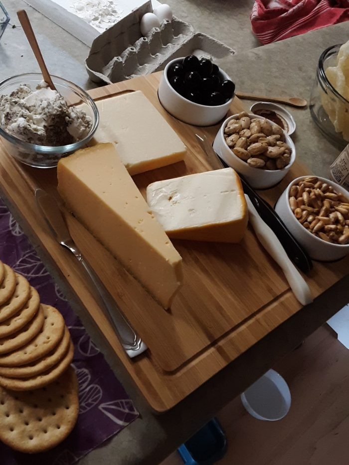 cheese board featuring several cheeses, nuts, and olives
