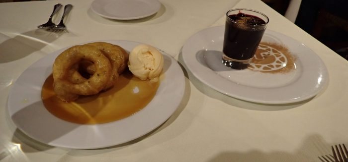 two dessert plates: one with donut-like pastries and one with a glass of purple pudding