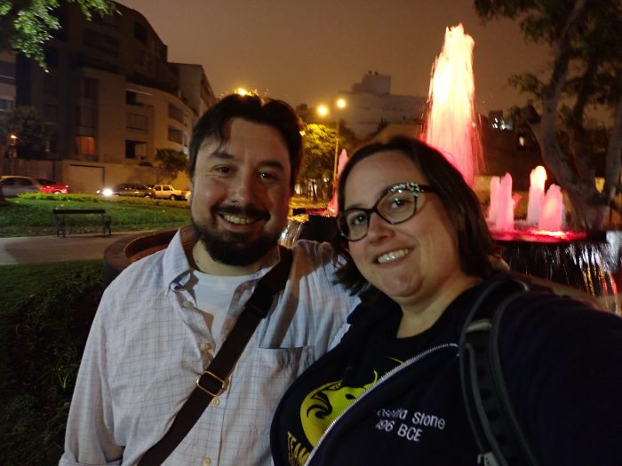 Kirk and in in front of an illuminated fountain at night