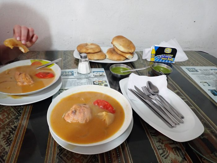 bowls of adobo soup and a plate of round breads