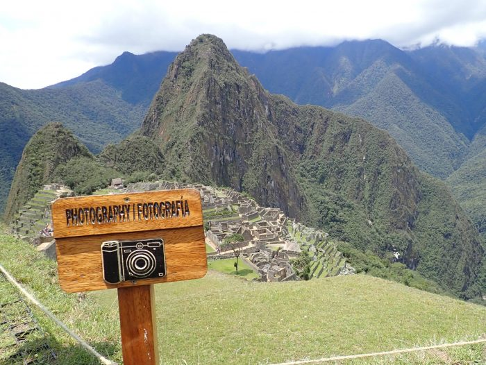 "a sign that says ""photograhpy"" in front of Machu Picchu"