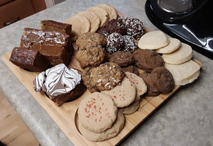 a wooden board covered in a variety of holiday cookies