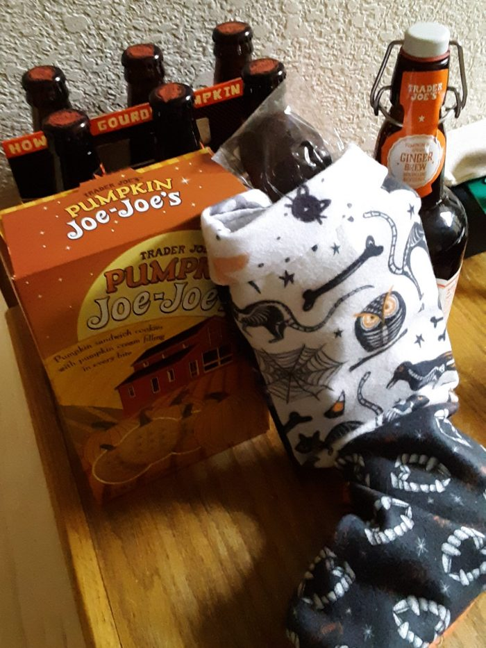 "a halloween-themed christmas stocking next to a box of ""pumpkin joe-joes"" and a six pack of pumpkin ale"