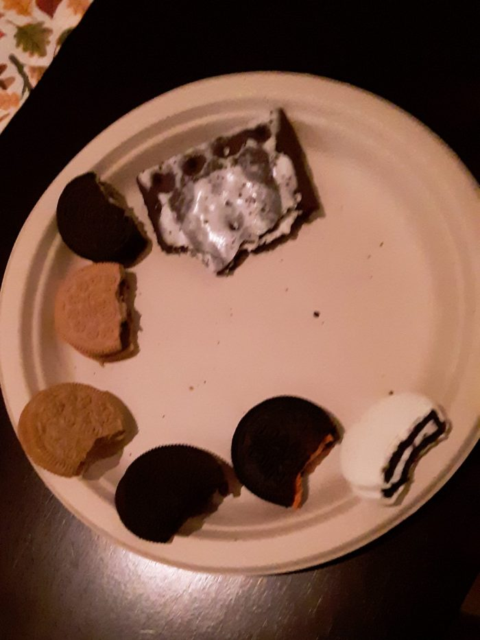 a paper plate of oreos each with a bite taken out of them