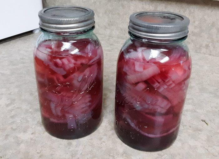 two large glass jars of pickled red onions