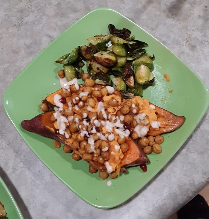a dinner plate with roasted brussels sprouts and a baked sweet potato covered in chickpeas and a tahini dressing