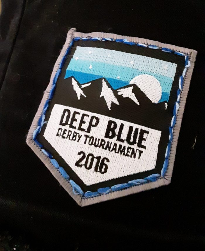 "a patch that says ""Deep Blue Derby Tournament 2016"" stitched onto a black vest using backstitch"