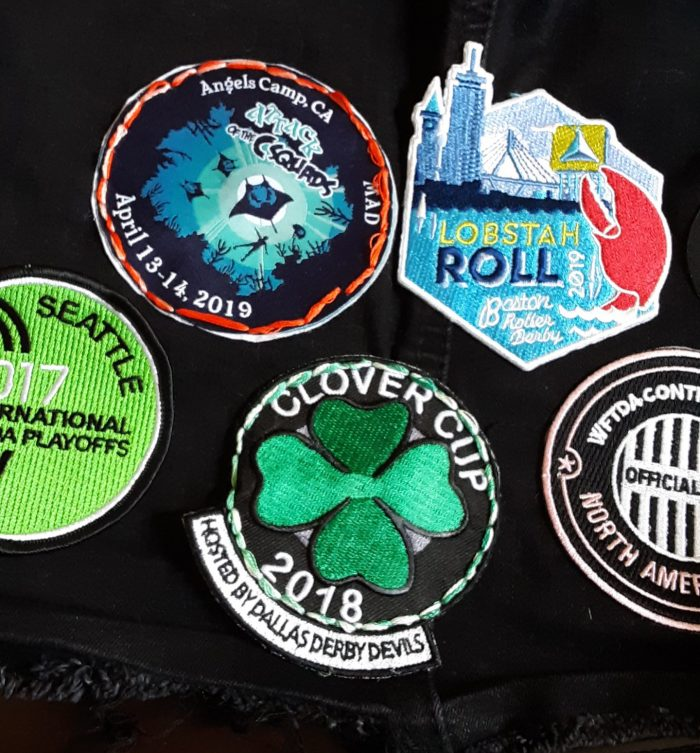 several patches on a black vest, including two hand stitched on