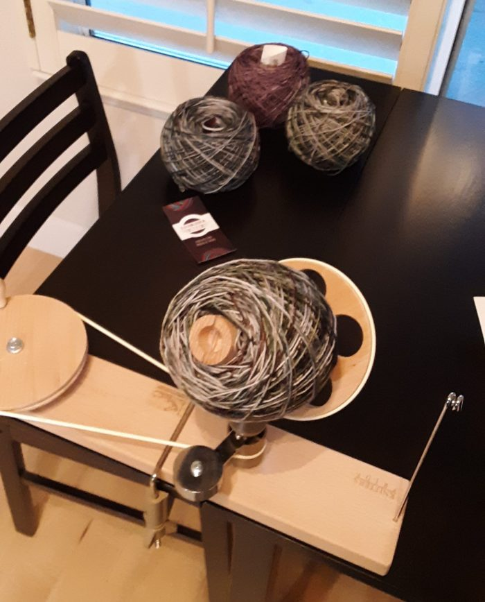 a wound ball of yarn on a hand-powered yarn winder