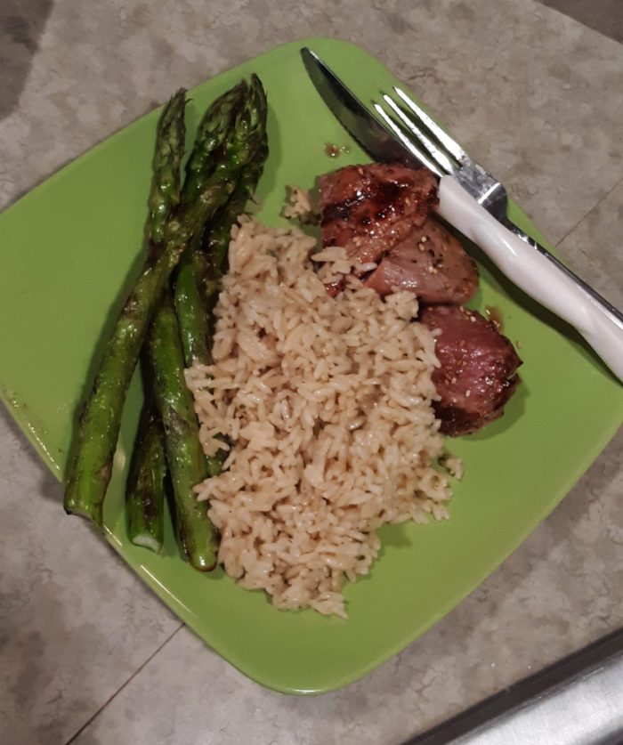 a plate of asparagas, rice, and pork tenderloin