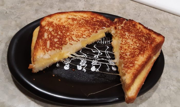 a grilled cheese sandwich cut into triangles to show a cheese stretch