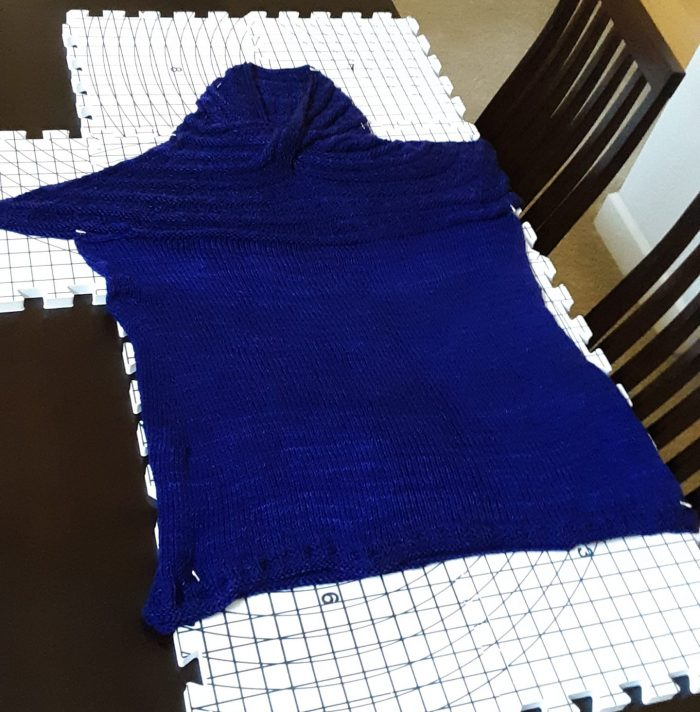 a handknit shirt laid out to dry and take shape