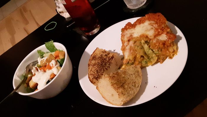 lasagne dinner: lasagna, garlic bread, salad and italian soda