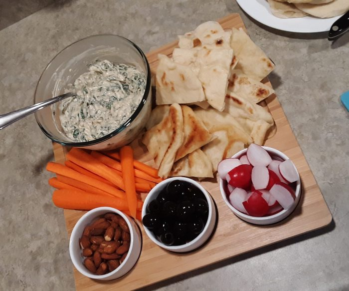 board with pita, spinach dip, carrot sticks, nuts, olives, and radishes