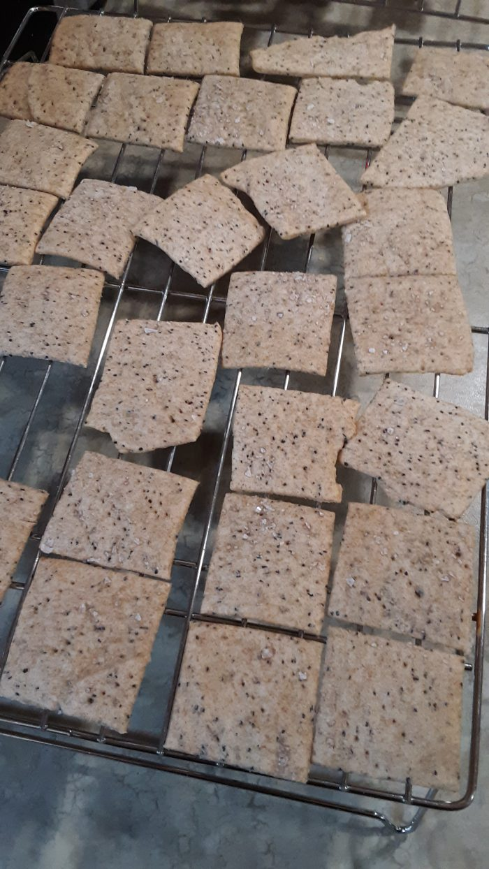 homemade poppyseed crackers on a wire cooling rack