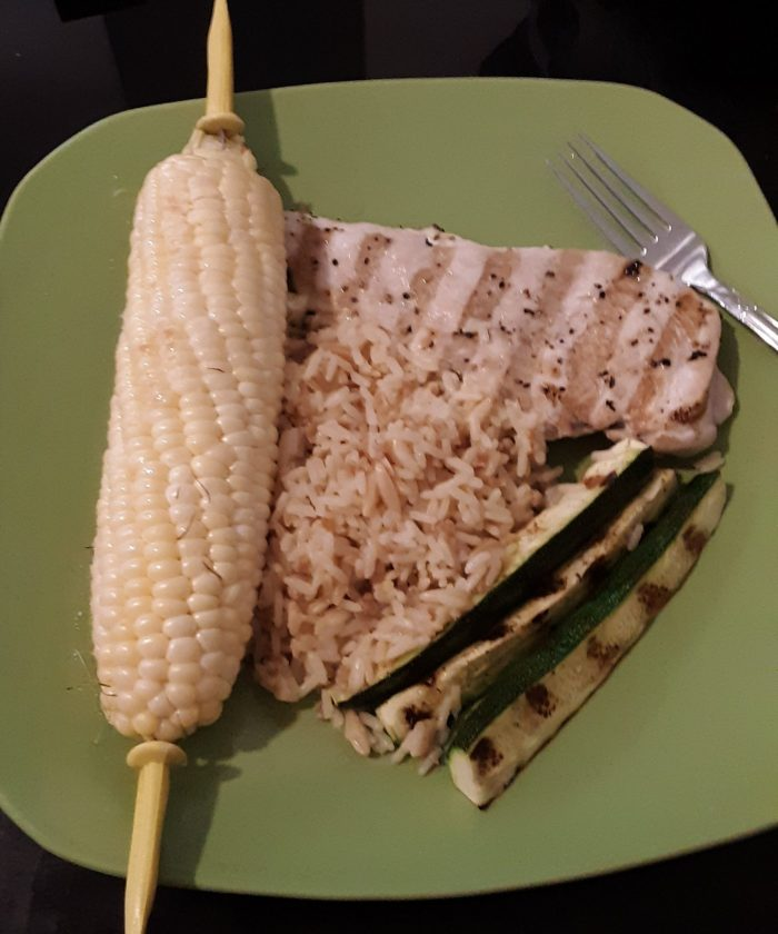 a plate of grilled chicken, zucchini, rice, and corn on the cob