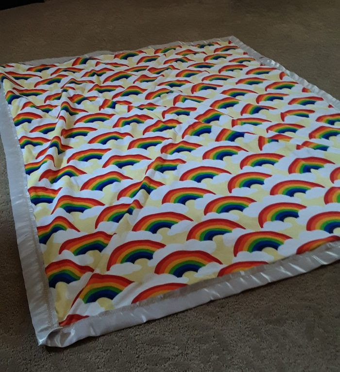soft side of the blanket in a cheerful rainbow fabric