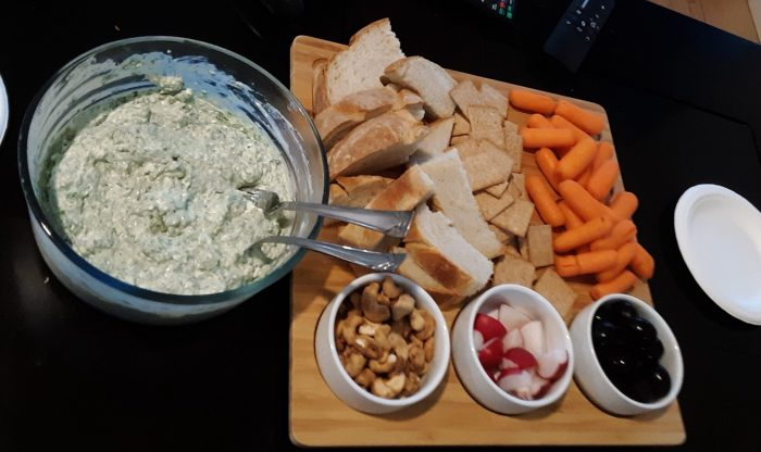spinach dip with an arrangement of bread, veggies and other snacks
