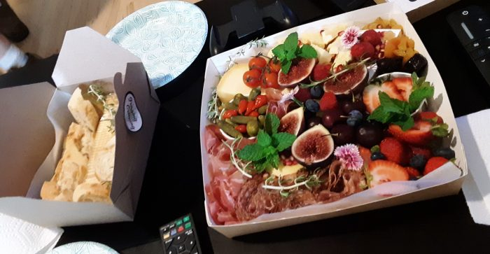a large box of charcuterie topped with lots of fruit, plus a smaller box of bread and crackers