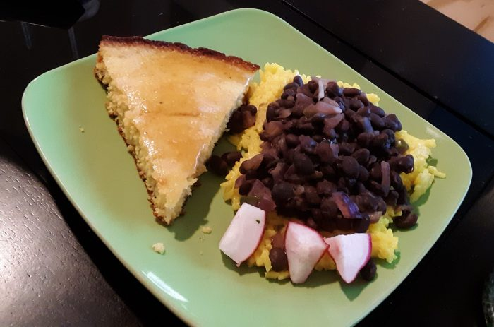 a plat with a pile of beans and rice next to a slice of cornbread