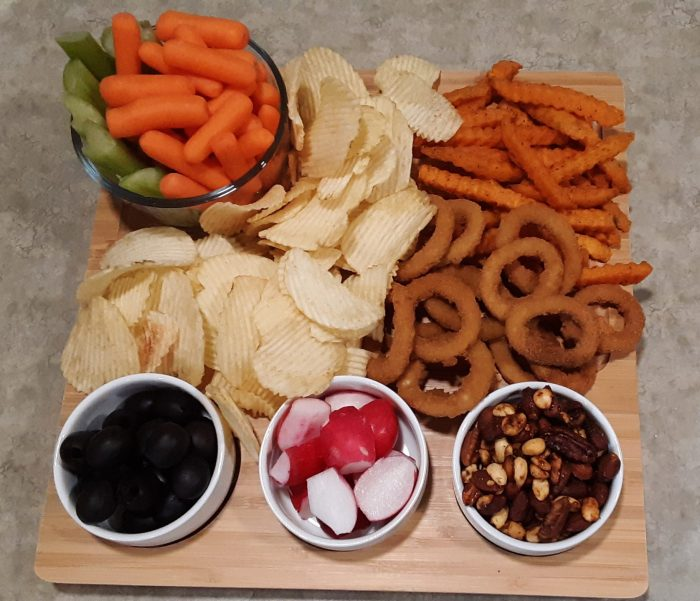 ranch dip snack board: veggies, chips, onion rings, nuts and olives