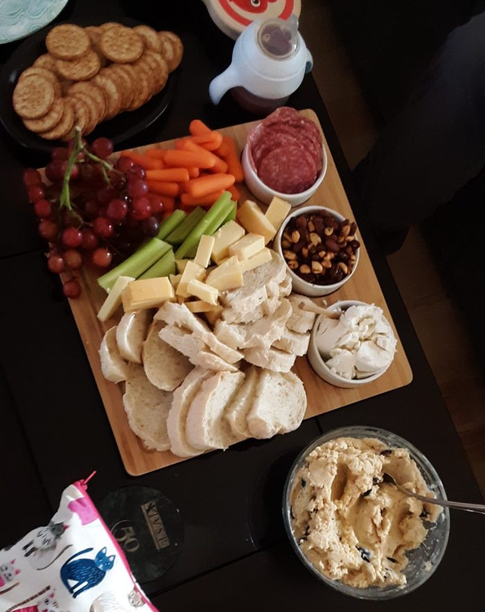 snack board featuring cheeses, sliced bread, grapges, vegetables, salame, crackers and dip
