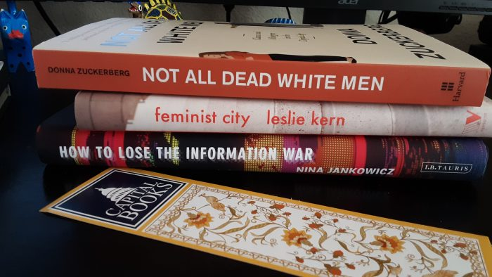a stack of three hardcover books: Not All Dead White Men, Feminist City, and How to Lose the Information War