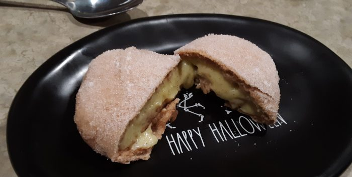 a vanilla cream bun cut in half to reveal the custard inside