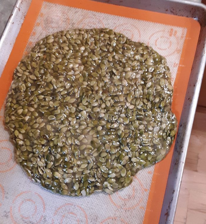 a large circle of pumpkin seed brittle, cooling on a sheet pan